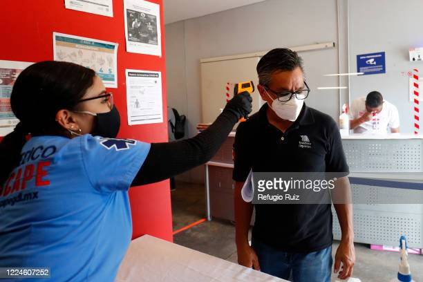 A paramedic measures the temperature to a memeber of the press as part of the COVID 19 protocol prior to the match between Mazatlan FC and Tigres...