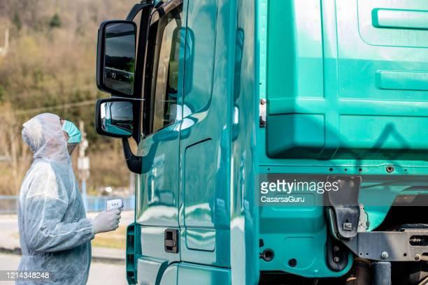 ドライバーテスト用赤外線温度計を使用したcovid-19危機時の国境管理の救急救命士 - 国境 ストックフォトと画像