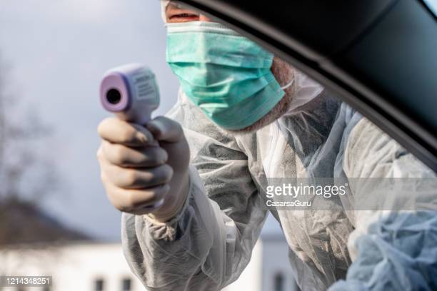 paramedic on border control during covid-19 crisis using infrared thermometer for drivers testing - infrared thermometer stock pictures, royalty-free photos & images
