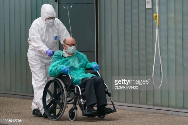 A paramedic pushes a man on a wheelchair outside the Burgos Hospital in Burgos in northern Spain on April 2 2020 The coronavirus death toll in Spain...