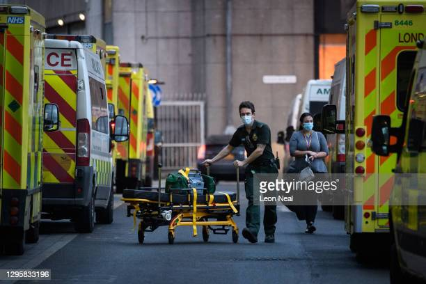 Paramedic pushes medical equipment back to his ambulance after delivering a patient to the Royal London hospital on January 11, 2021 in London,...