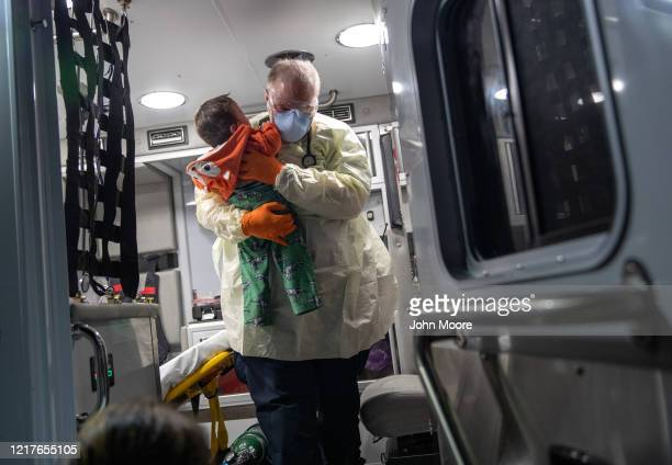 Paramedic Randy Lilly, wearing personal protection equipment , carries a 10-month-old boy with fever after arriving by ambulance to Stamford Hospital...