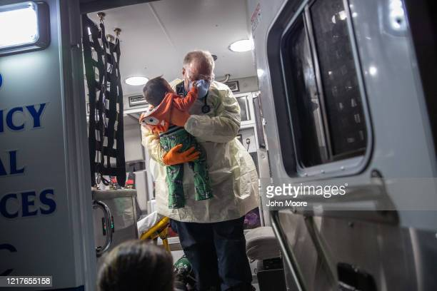 Paramedic Randy Lilly wearing personal protection equipment carries a 10monthold boy with fever after arriving by ambulance to Stamford Hospital on...