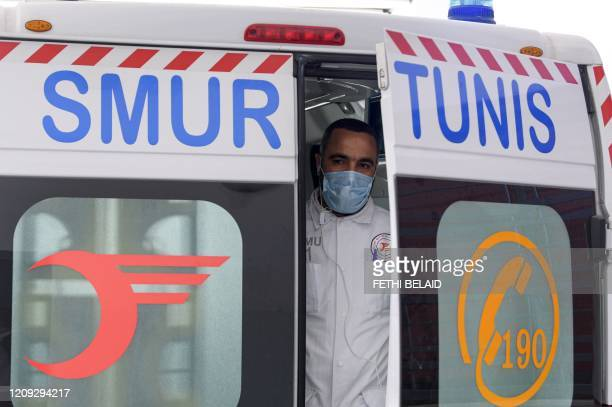 A paramedic rescuer of SAMU Tunisia wearing a surgical mask as a precaution against COVID19 coronavirus disease looks out from the back of an...