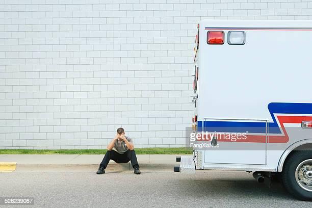 Rettungssanitäter sitzen auf Boden mit Kopf in den Händen