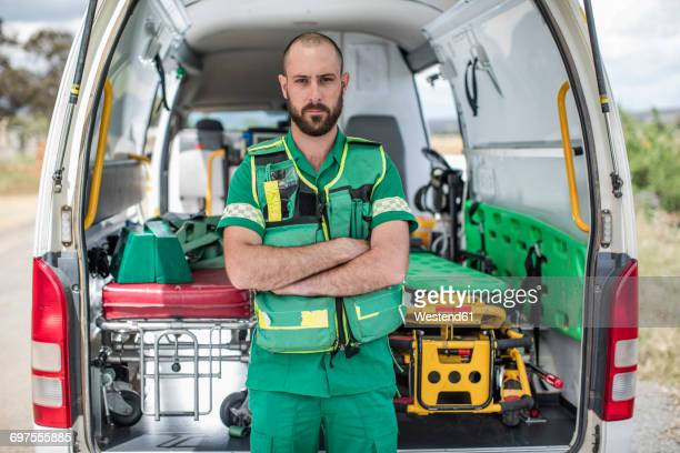 Paramedic standing with arms crossed in front of ambulance