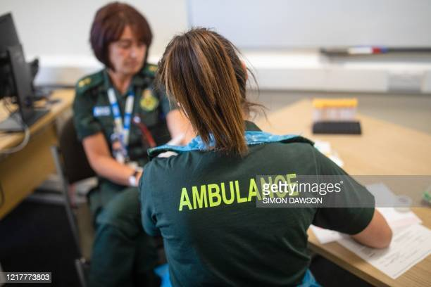 Paramedic takes a blood sample from a front line ambulance worker during an antibody testing programme at the Hollymore Ambulance Hub of the West...