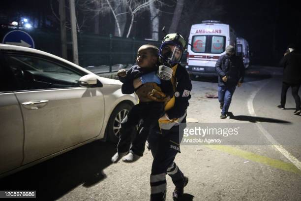 Paramedic takes an asylum seeker baby suffering from gas inhalation to the hospital tent after Greek police as Greek security forces use tear gas and...