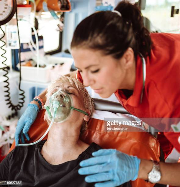 paramedic taking care of a woman in the ambulance for covid-19 - oxygen mask stock pictures, royalty-free photos & images