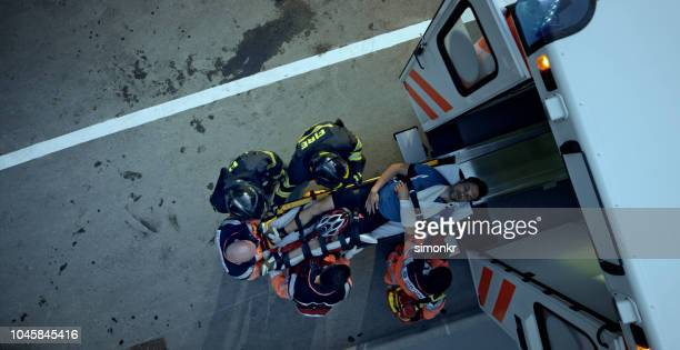 paramedic team and firemen loading injured male cyclist on stretcher into ambulance - ambulance stock pictures, royalty-free photos & images