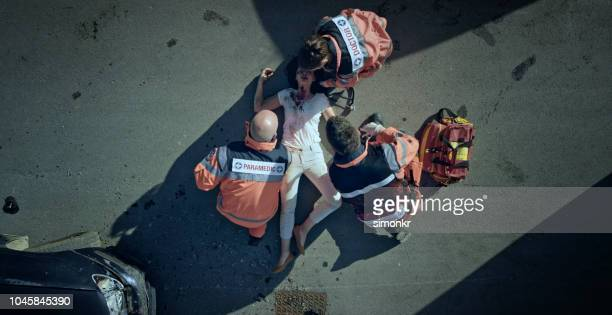 paramedic team checking vital signs of car accident victim lying on ground at car crash site - rescue worker stock pictures, royalty-free photos & images