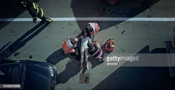 überprüfung der vitalfunktionen von auto unfallopfer auf boden an auto-absturzstelle sanitäter-team - verbrechensopfer stock-fotos und bilder