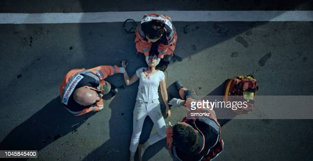 paramedic team checking vital signs of car accident victim lying on ground at car crash site - crash site stock pictures, royalty-free photos & images