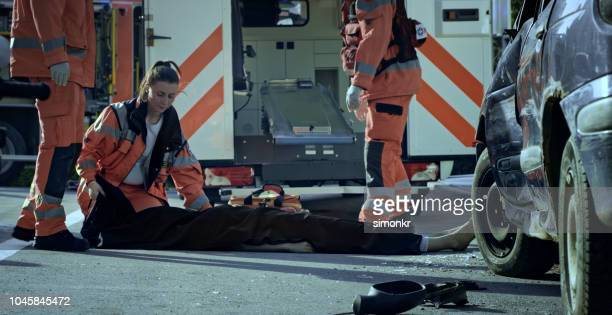 paramedic team covering body of car crash victim with black sheet - of dead people in car accidents stock pictures, royalty-free photos & images
