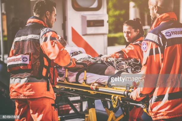 paramedic team helping injured person - rescue worker stock photos and pictures