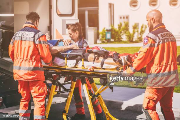 paramedic team helping injured person - concussion stock photos and pictures