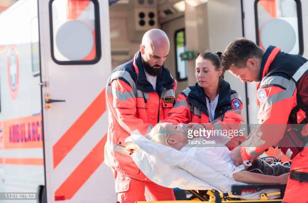paramedic team helping injured woman - ambulance stock pictures, royalty-free photos & images