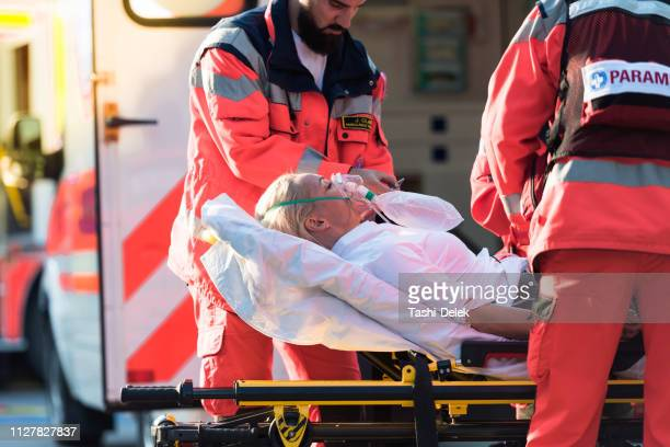 paramedic team helping injured woman - oxygen mask stock pictures, royalty-free photos & images