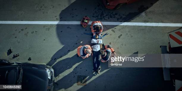 paramedic team immobilizing male injured in car crash - car accident stock pictures, royalty-free photos & images