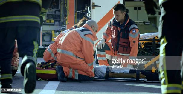 paramedic team immobilizing male injured in car crash - black glove stock pictures, royalty-free photos & images