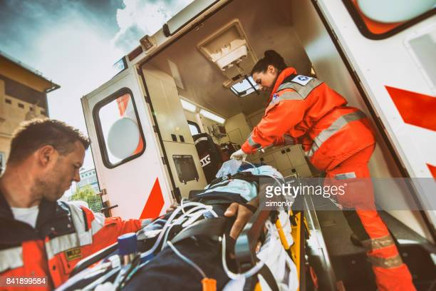 paramedic team pushing stretcher - rescue services occupation stock pictures, royalty-free photos & images
