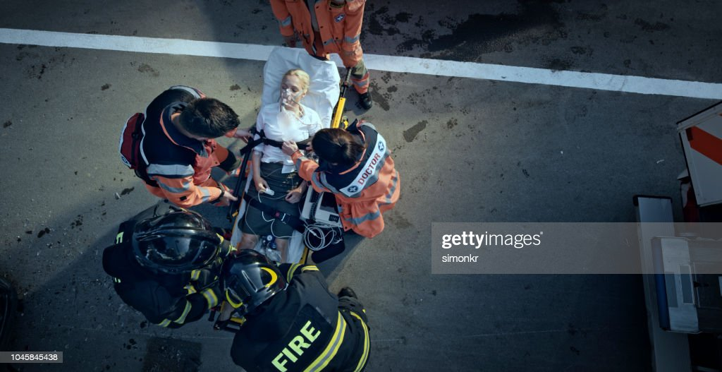 Paramedic team stabilizing injured woman on stretcher at scene of accident : Stock Photo