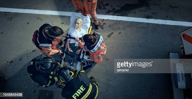 paramedic team stabilizing injured woman on stretcher at scene of accident - rescue worker stock pictures, royalty-free photos & images