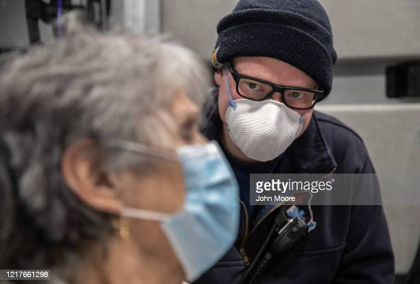 Paramedic watches over Janet Gazo while transporting her by ambulance to Stamford Hospital on April 03, 2020 in Stamford, Connecticut. Gazo, who...