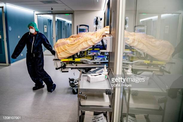 A paramedic wearing a face mask and gloves moves a patient on a stretcher to be transferred to another hospital due to overload amid Coronavirus...