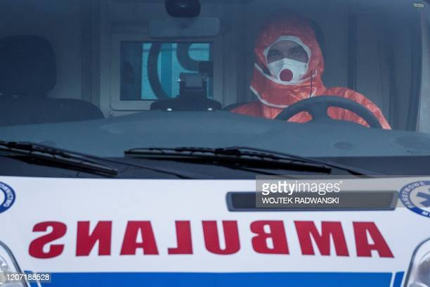 Paramedic, wearing a protective outfit, sits in an ambulance at an infectious hospital in Warsaw, on March 14, 2020. - Polish government urged...