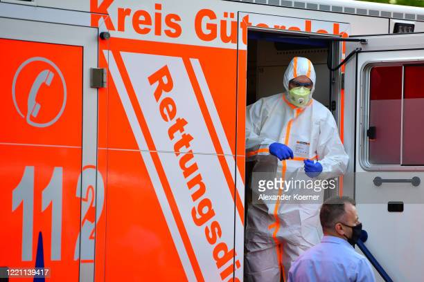 Paramedic wearing full body protection stands inside an ambulance whilce local police forces secure an apartment complex used by the Toennies meat...