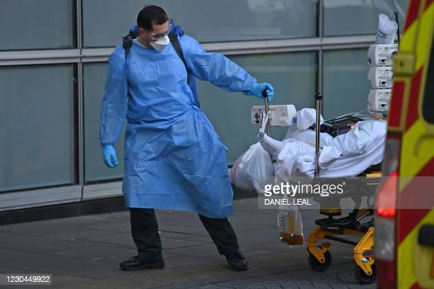 Paramedic wearing full PPE unloads a patient from an ambulance outside the Royal London Hospital in east London on January 6, 2021. - Britain...