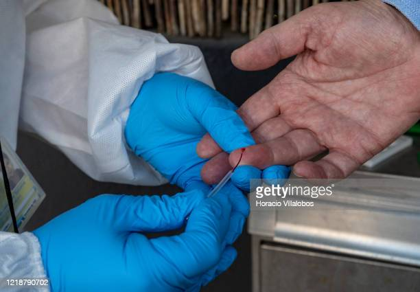 A paramedic wearing protective gear collects capillary blood while testing residents at their homes for coronavirus in order to learn more about how...