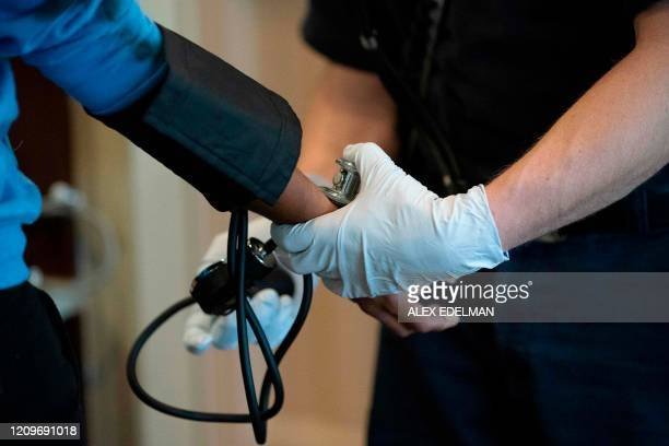 A paramedic with Anne Arundel County Fire Department takes the blood pressure of a patient as he responds to a medical call on April 9 2020 in Glen...