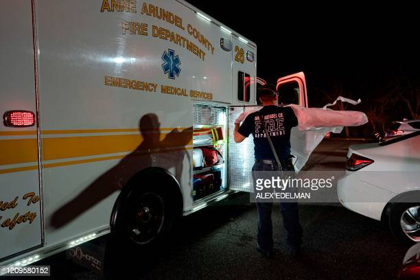 A paramedic with the Anne Arundel County Fire Department puts on a gown while responding to a 911 call for a suspected COVID19 patient on April 9...