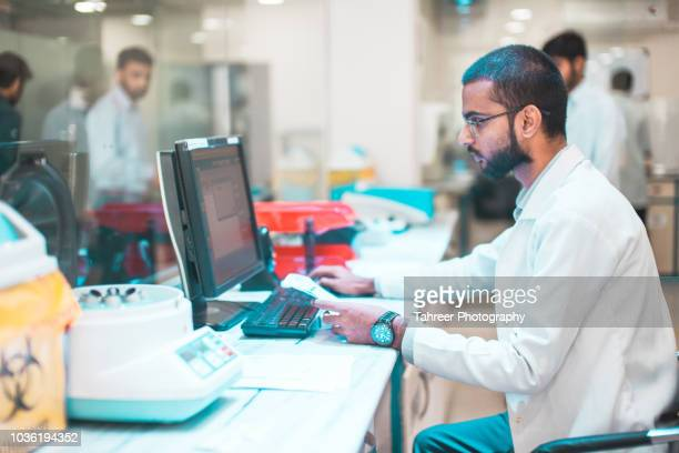 a paramedic working on computer in a medical lab - biochemistry stock pictures, royalty-free photos & images