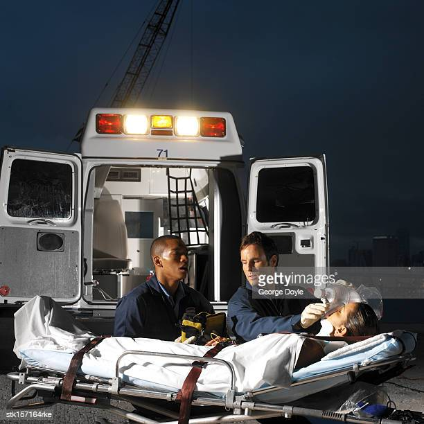 paramedics administering oxygen to a patient at an outdoor location