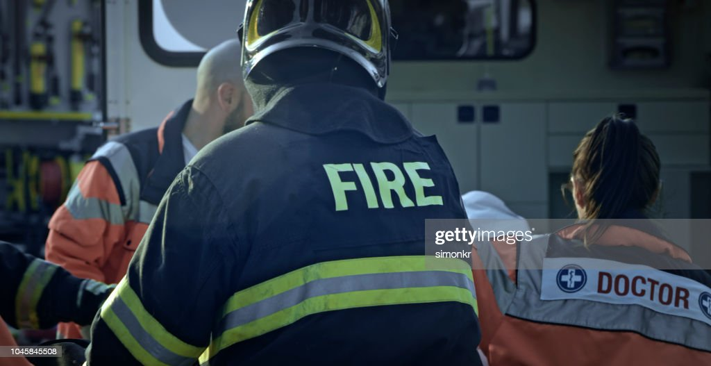 Paramedics and firefighters at car accident : Stock Photo