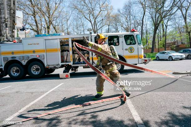 Paramedics and firefighters with the Anne Arundel County Fire Department arrive on the scene after responding to a 911 call for a structure fire on...