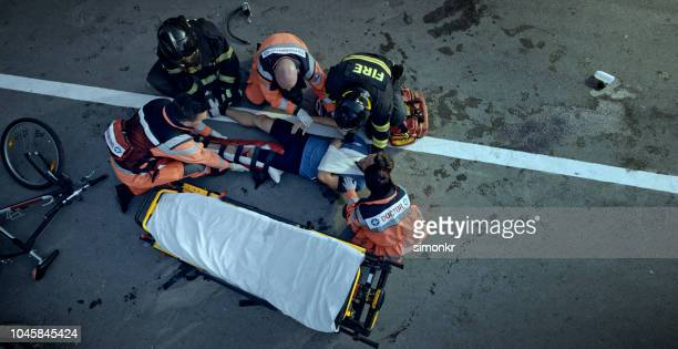 paramedics and firemen raising an injured male cyclist onto stretcher at scene of accident - wreck stock pictures, royalty-free photos & images