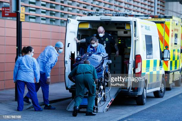 Paramedics and medical staff remove a stretcher loaded with equipment from an ambulance outside the emergency department of the Royal London Hospital...