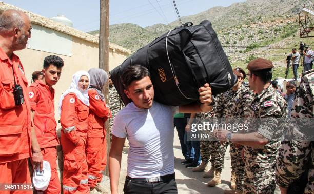 Paramedics and members of the Lebanese General Security Directorate stand by as Syrian refugees are evacuated from the southern Lebanese village of...