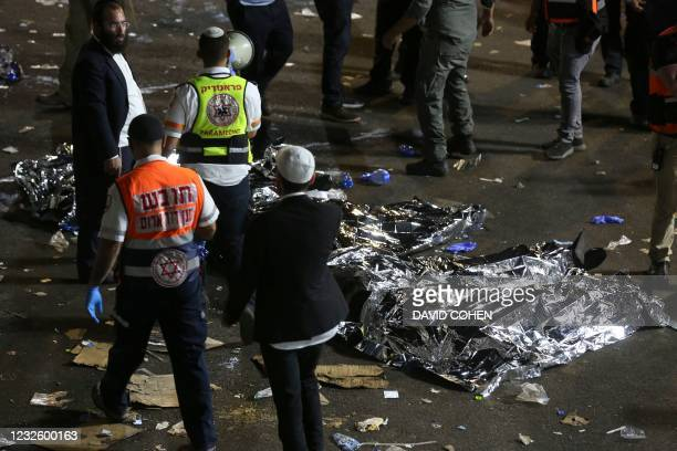 Paramedics and ultra-Orthodox Jewish men stand next to covered bodies after dozens of people were killed and others injured after a grandstand...