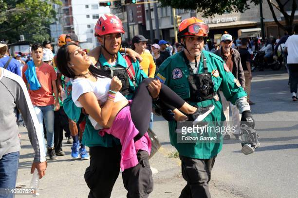Paramedics assist a proJuan Guaidó demonstrator who was injured in a clash with police forces after the May 1 demonstration near plaza Altamira on...