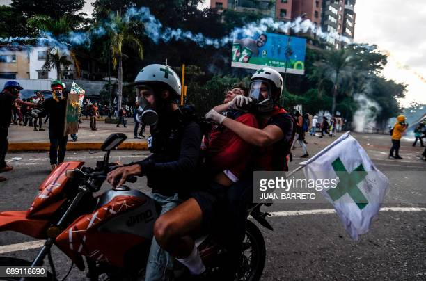 TOPSHOT Paramedics assist an antigovernment demonstrator injured in a clash with riot police during a demonstration against Venezuelan President...