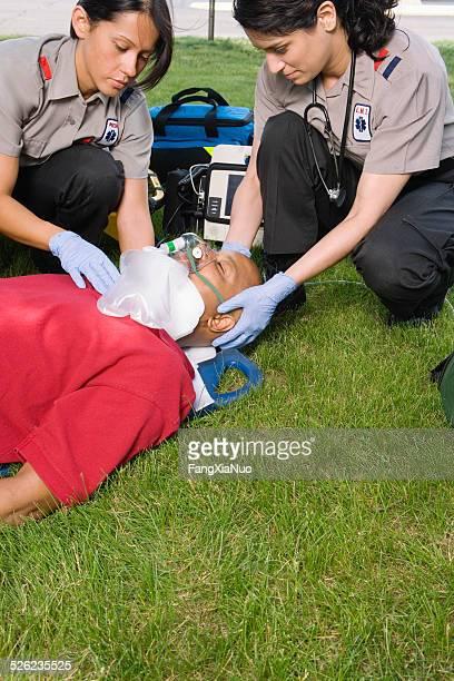 paramedics di fissaggio del collare del paziente sull'erba - helicopter emergency foto e immagini stock