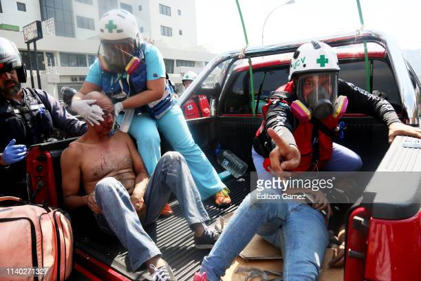 Paramedics attend two proGuaidó demonstrators who were wounded in a clash with police forces on April 30 2019 in Caracas Venezuela Through a live...