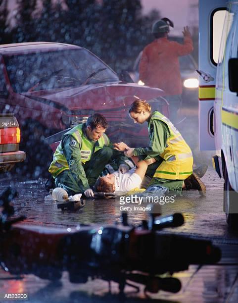 Paramedics attending to victim at scene of car crash