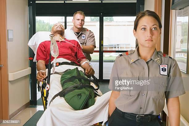 Paramedics bringing patient on stretcher into hospital