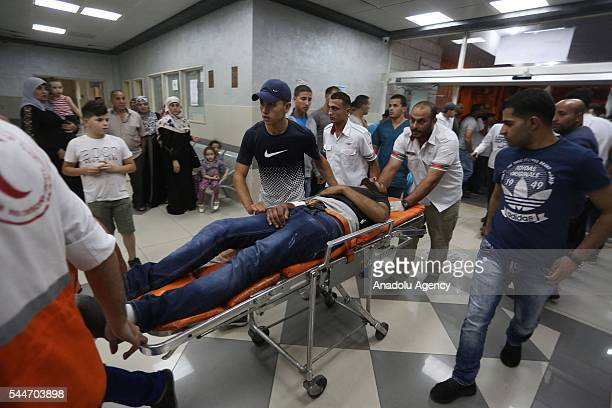 Paramedics carry 4 injured Palestinians after the clashes against Israeli forces who have been destroyed 2 Palestinian houses at Qalandia refugee...